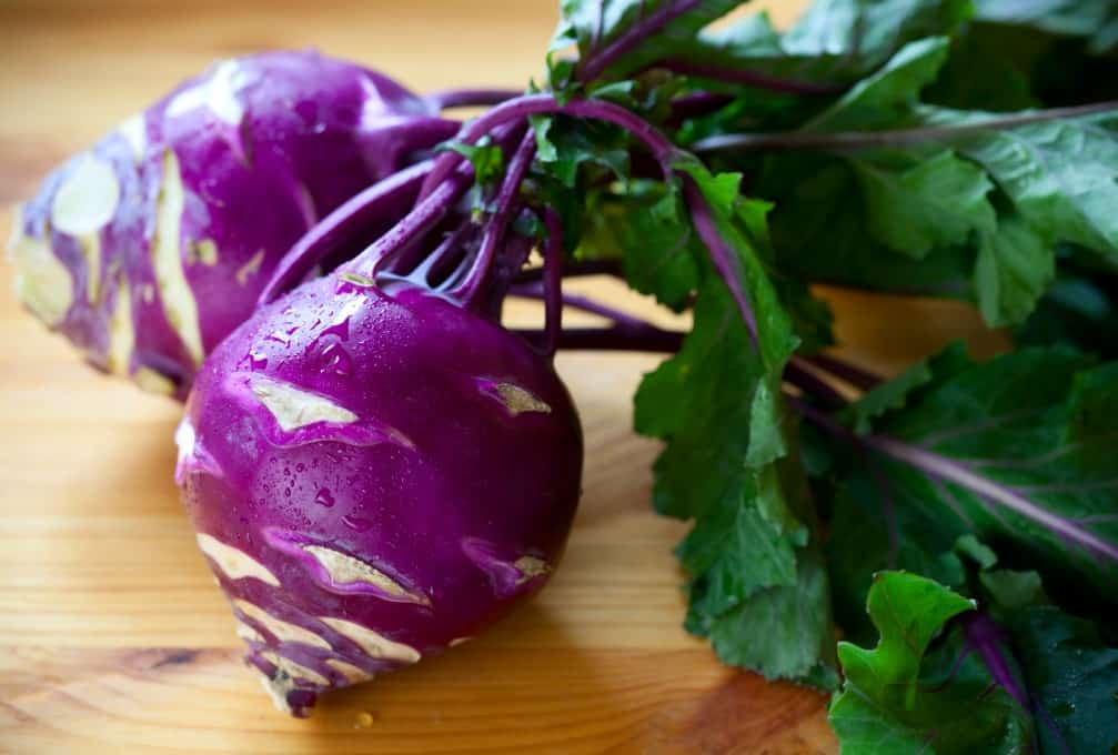 Fresh purple kohlrabi with leaves on a wooden table