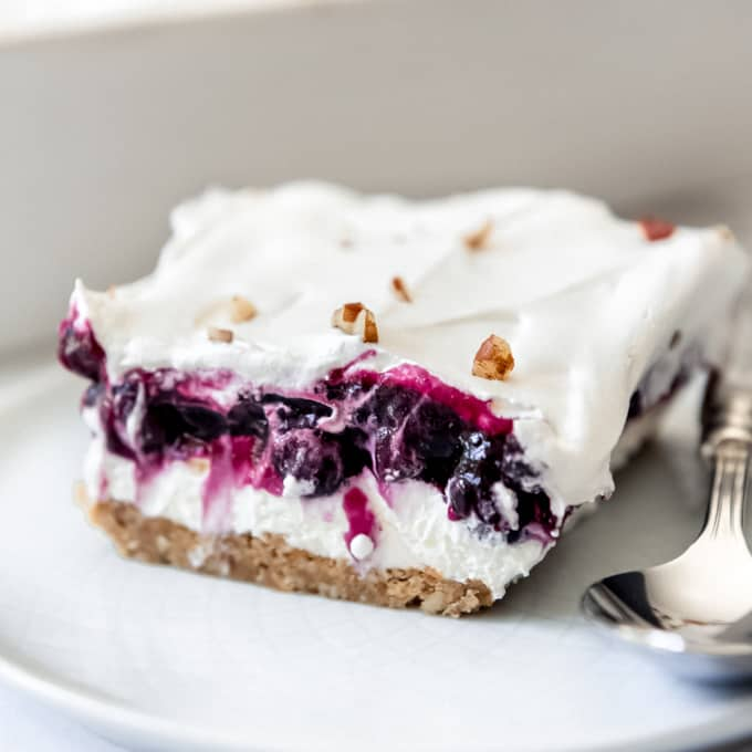 Blueberry Delight - a slice of layered no-bake blueberry cream cheese dessert on a plate with a spoon.
