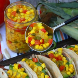 A spoon holds brightly coloured corn, red peppers, and jalapeno relish above tacos.