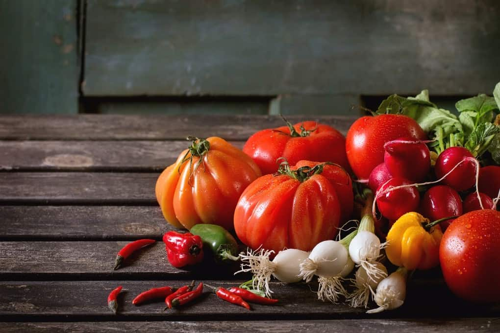 Heap of fresh ripe colorful vegetables tomatoes, chili peppers, green onion and bunch of radish over old wooden table. Dark rustic atmosphere
