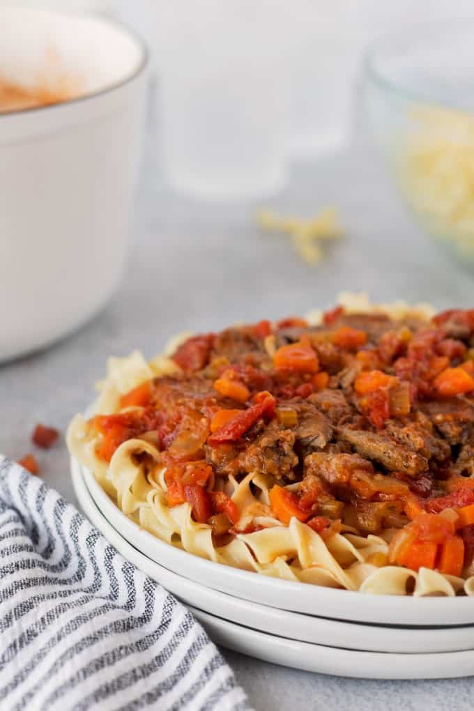 Plateful of Swiss steak over noodles
