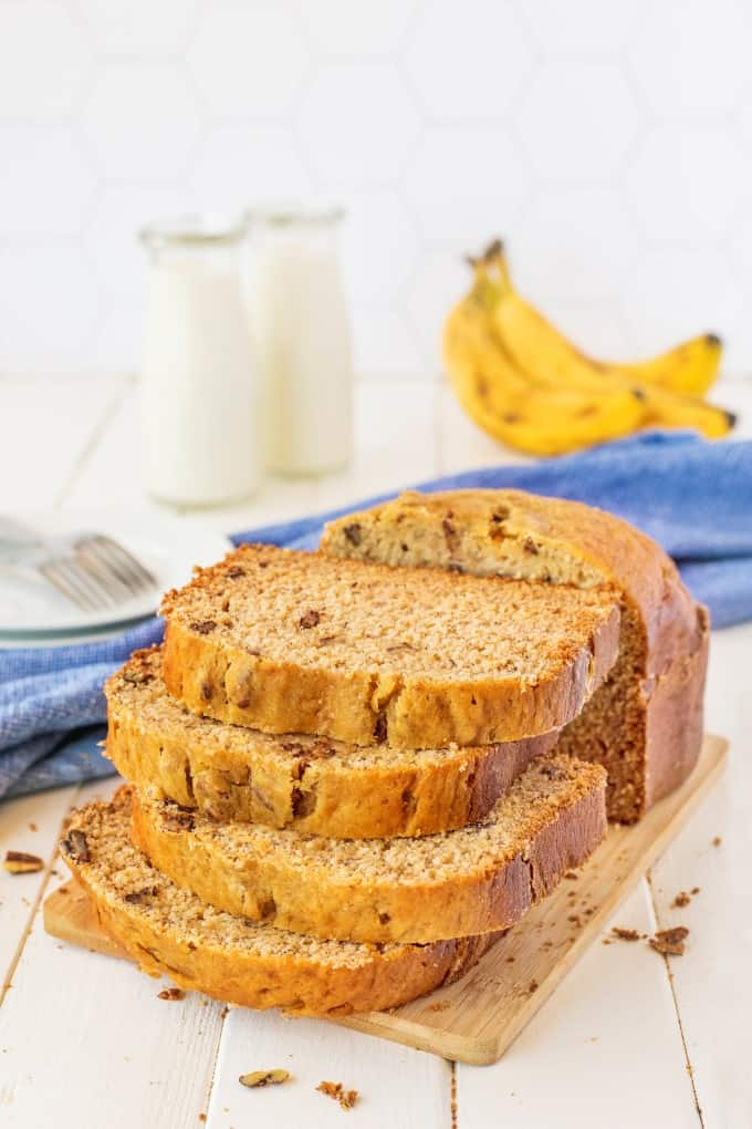 Stacked banana bread on a wooden board with milk and bananas in the background.