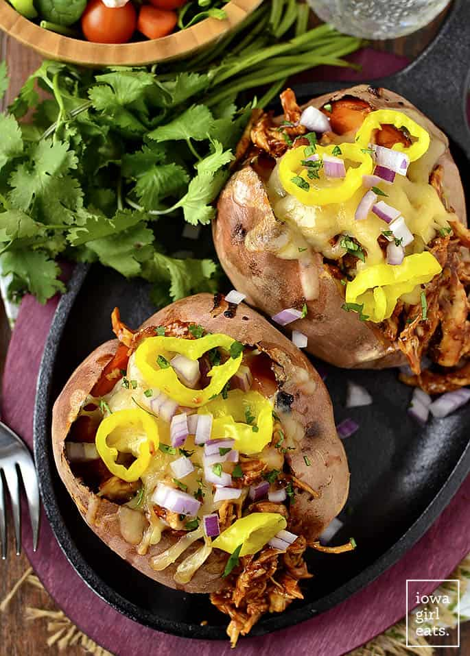 BBQ Chicken stuffed sweet potatoes on a black skillet with a bunch of parsly and a fork