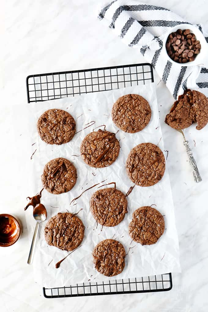 Brownie cookies on parchment paper on a cooling rack.