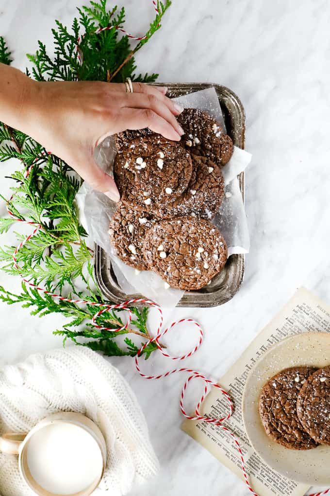 Overhead shot of brownie cookies with a hand grabbing one and greenery and white and red thread.