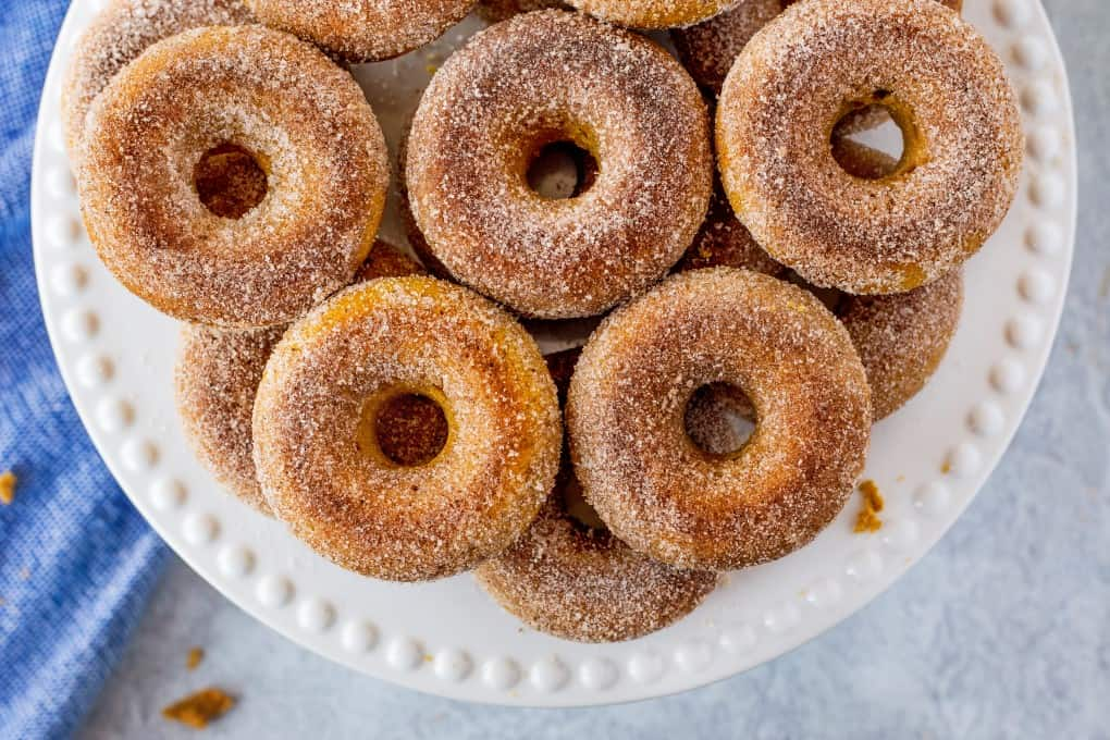 Baked Pumpkin Donuts on a white plate, overhead shot.