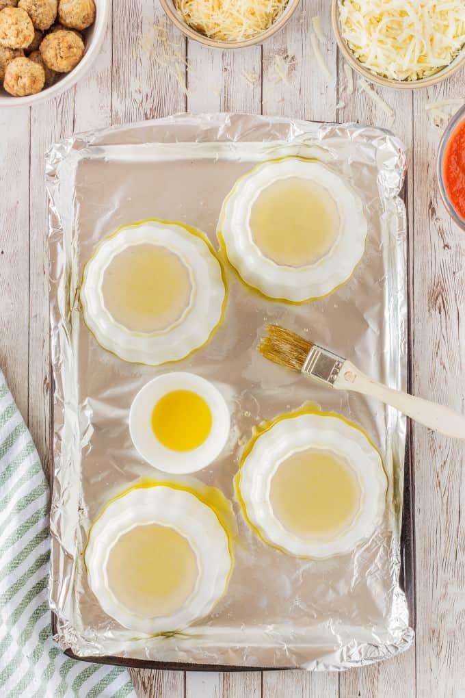 Ramekins upside down on a foil lined baking sheet painted in oil.