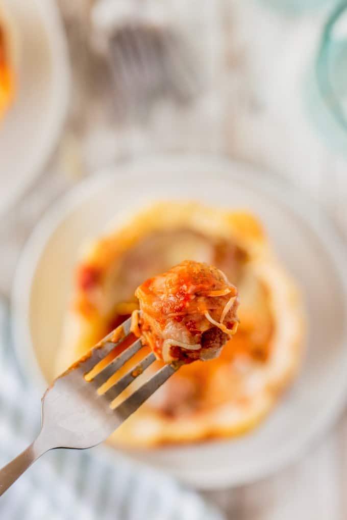 Closeup of a cheesy meatball on a fork.
