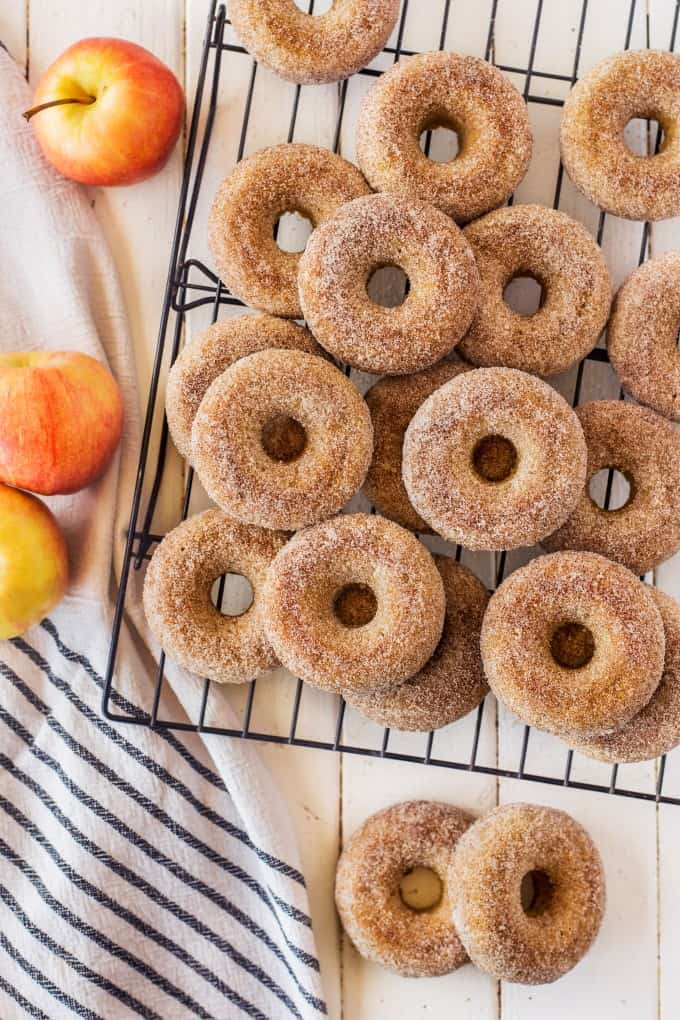 Donuts on a cooling rack with apples and linens