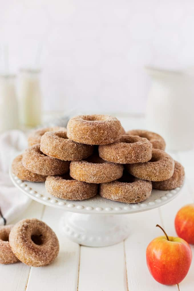 Apple Cider Donuts stacked like a pyramid on a cake tray with apples and donuts below it.
