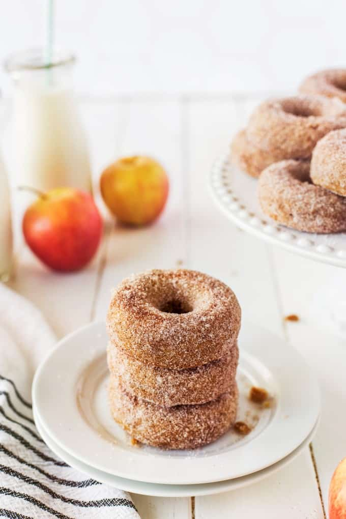 Donuts stacked on a plate with apples and a cake stand of donuts in the background.