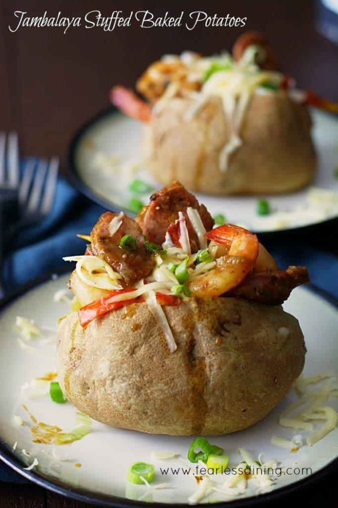 Mardi Gras Jambalaya Stuffed Baked Potato on a white and blue plate with chopped green onions