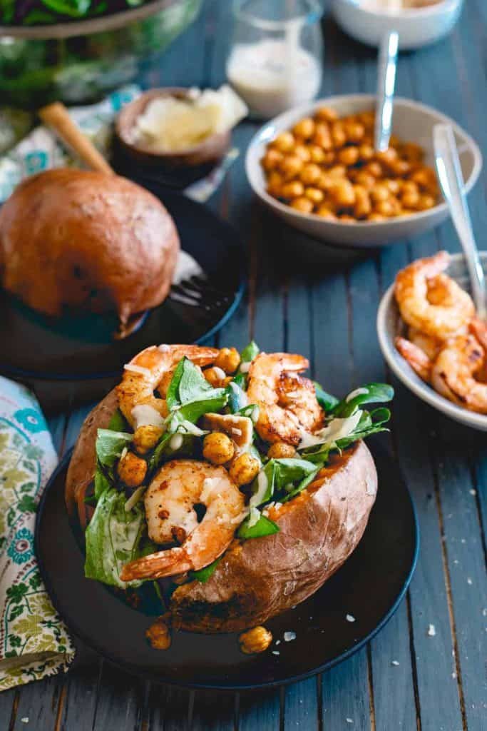 Caesar Salad Stuffed Sweet Potatoes With Spicy Shrimp on a small black plate with a bowl of shrimp and chickpeas beside it