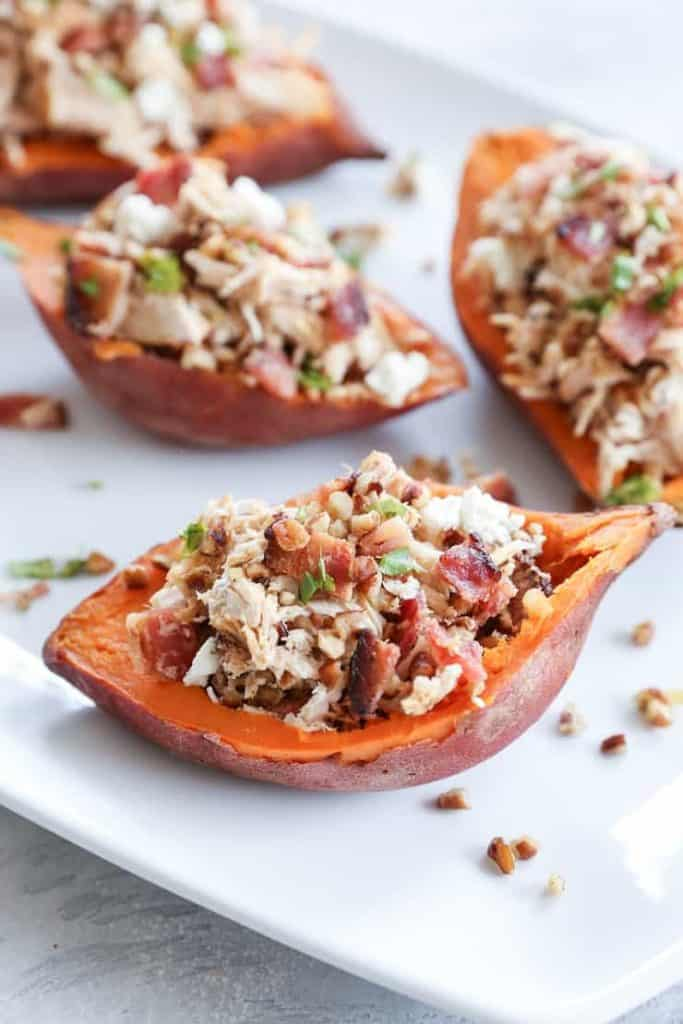 Loaded Sweet Potato Skins with Pecans, Chicken, and Bacon on a white platter