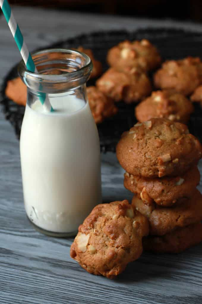 A stack of golden cookies next to a bottle containing milk and a straw.