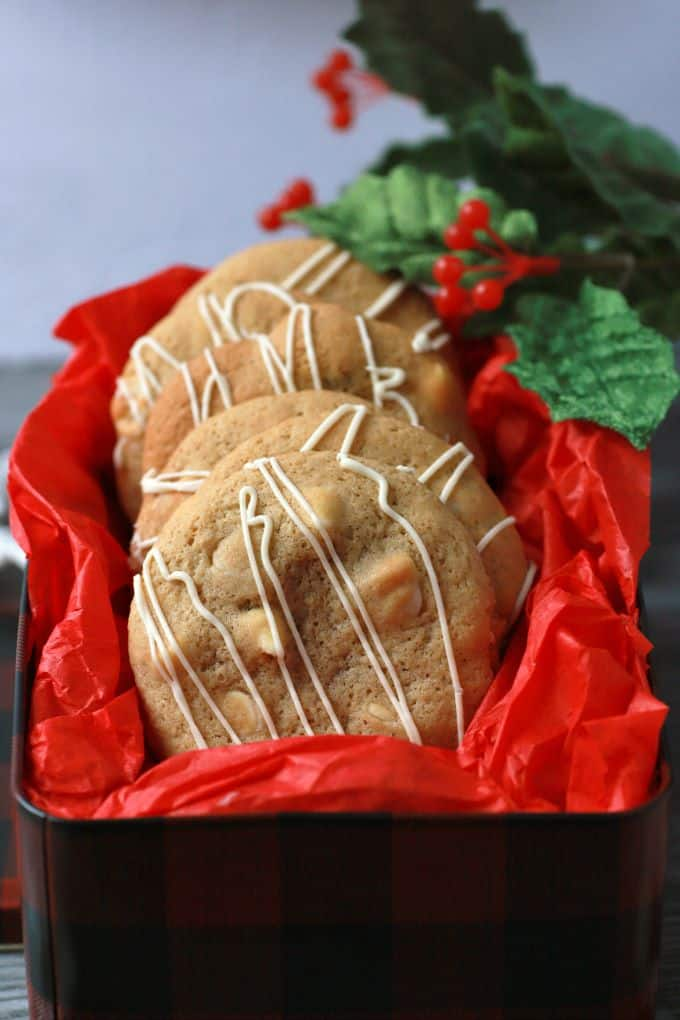 Golden baked cookies with white drizzle in a red tissue paper lined cookie tin.