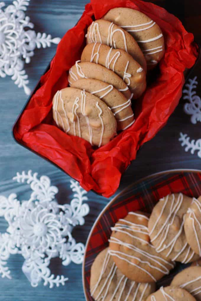 Golden baked cookies with white drizzle in a red tissue paper lined cookie tin surrounded by snowflakes.