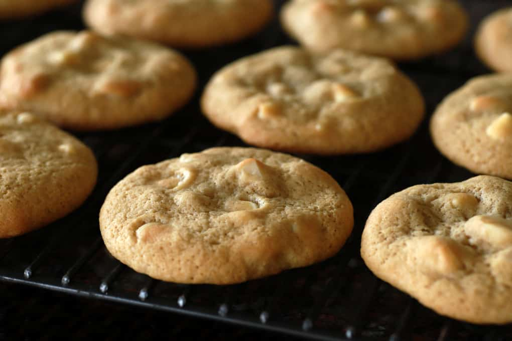 Golden baked cookies cooling on a black cookie rack.