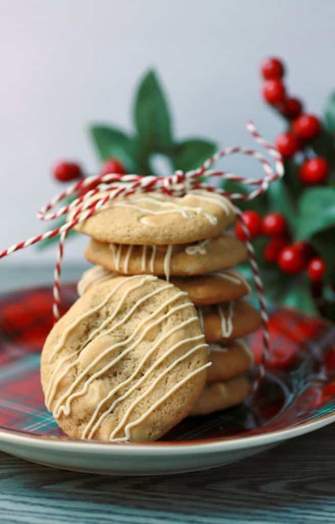 A stack of golden baked cookies tied with red and white twine with another cookie leaning on the stack.