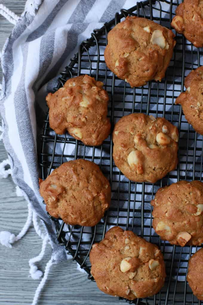 Baked tropical coconut granola cookies on a round black baking rack.