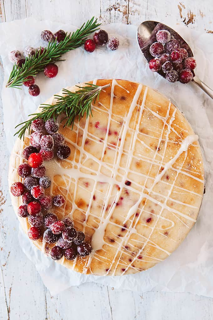 Cranberry White Chocolate Cheesecake on parchment paper on a white board decorated with cranberries and rosemary.
