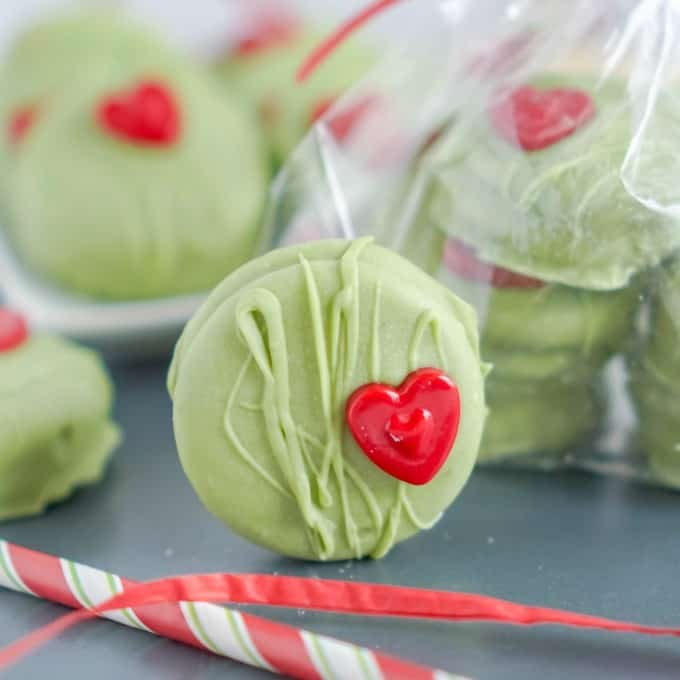 Grinch Cookies standing up with some packaged in the background.