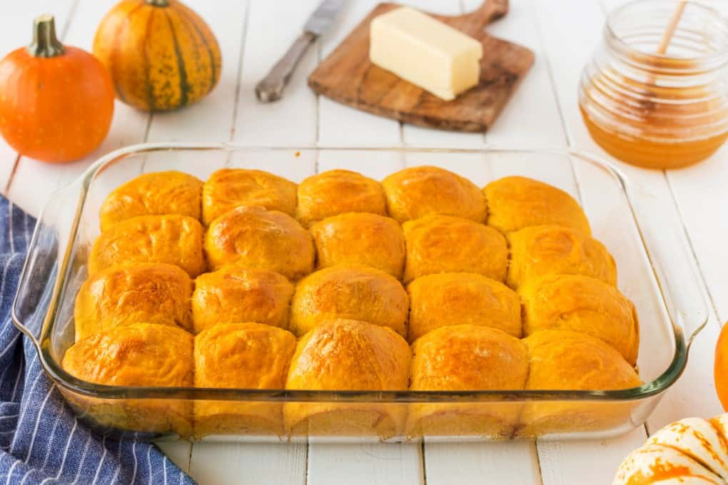 Dinner rolls in a glass pan with pumpkins, butter and honey in the background.