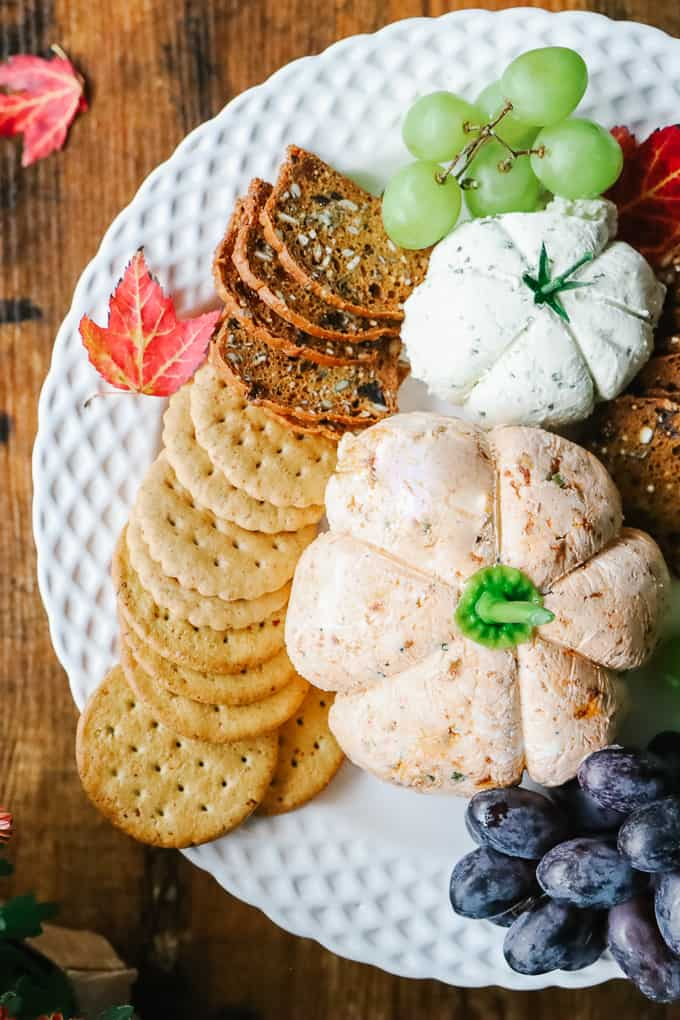 Cheese balls on a plate with crackers and grapes.