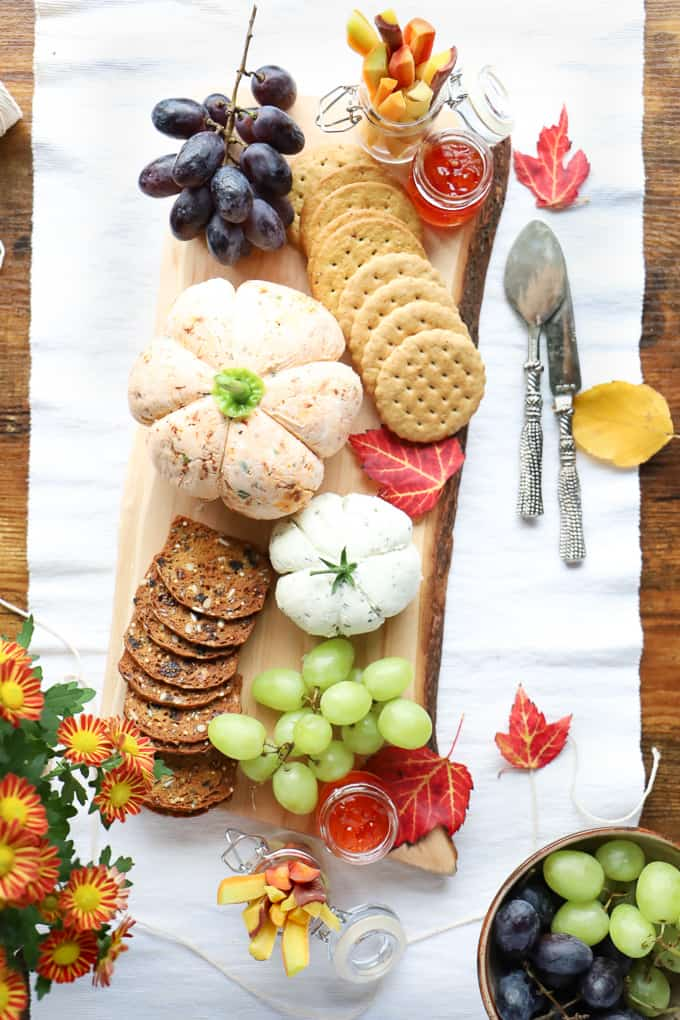 Overhead shot of a cheeseboard with two pumpkin cheese balls, crackers, fruit etc.