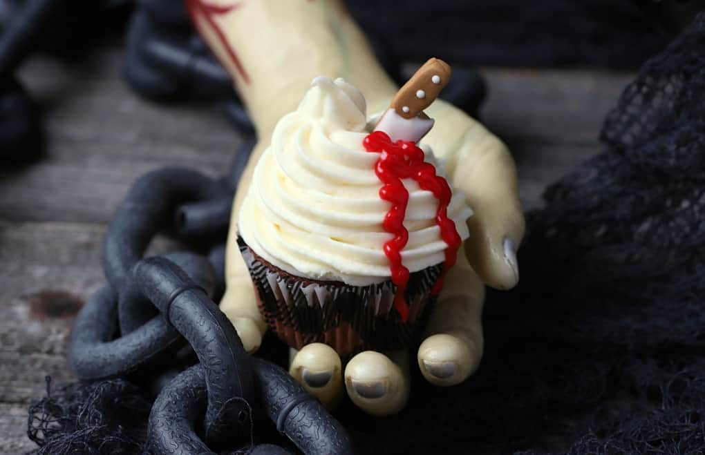 A bloody hand holds a cupcake topped with swirled white frosting oozing blood from a candy knife.