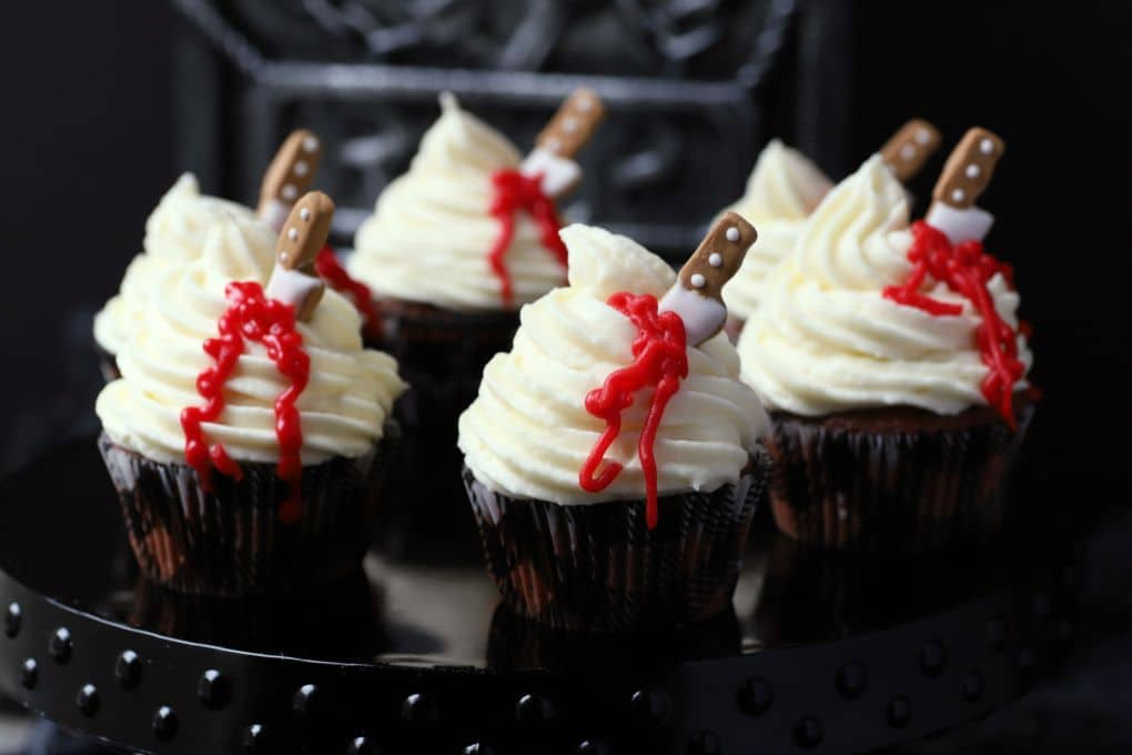 A platter of cupcakes topped with swirled white frosting oozing blood from a candy knife.