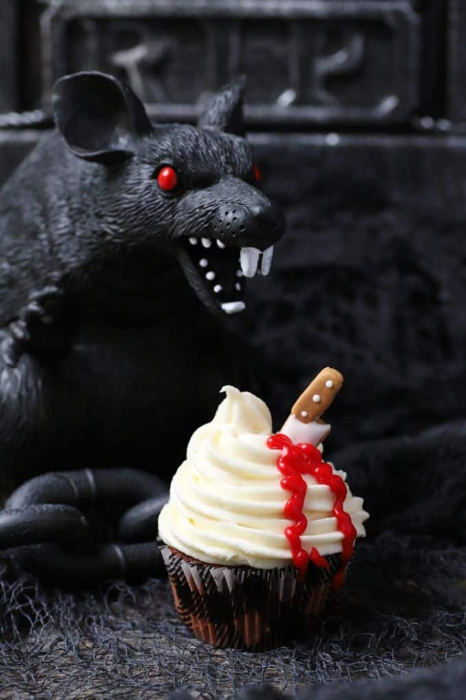 A black plastic rat hovers over a bleeding cupcake.