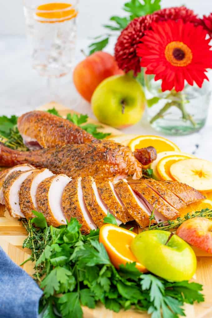 Sliced turkey on a board with sliced apples and oranges and herbs