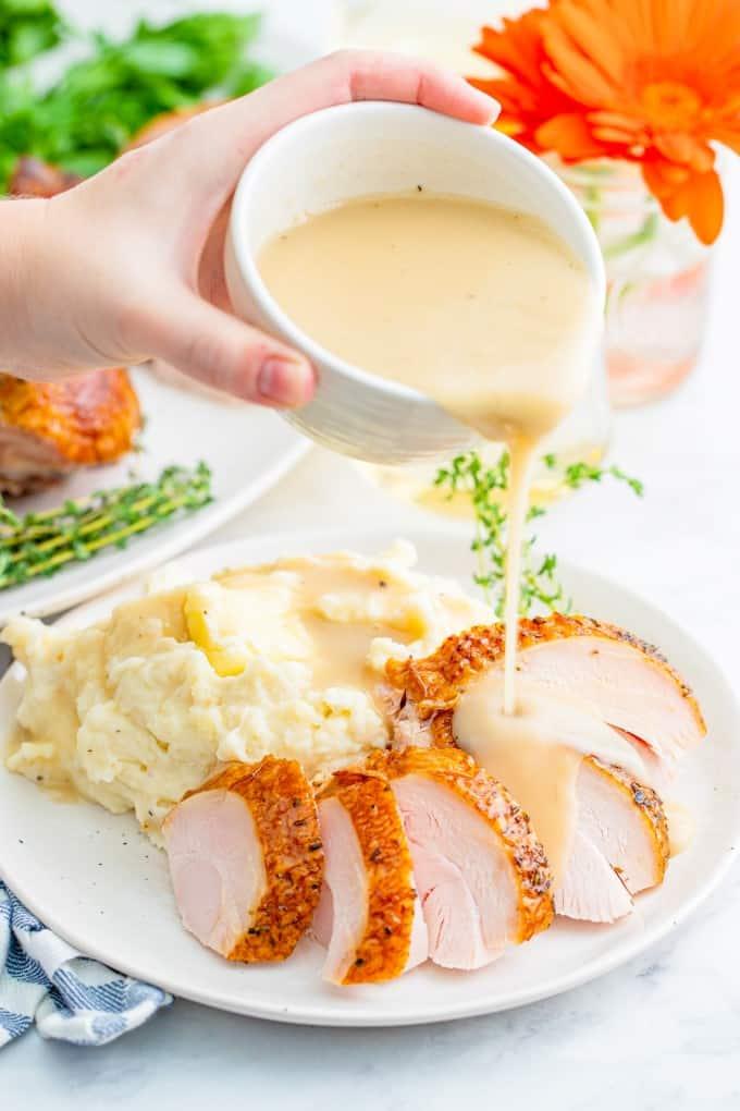 Pouring gravy on sliced turkey breast