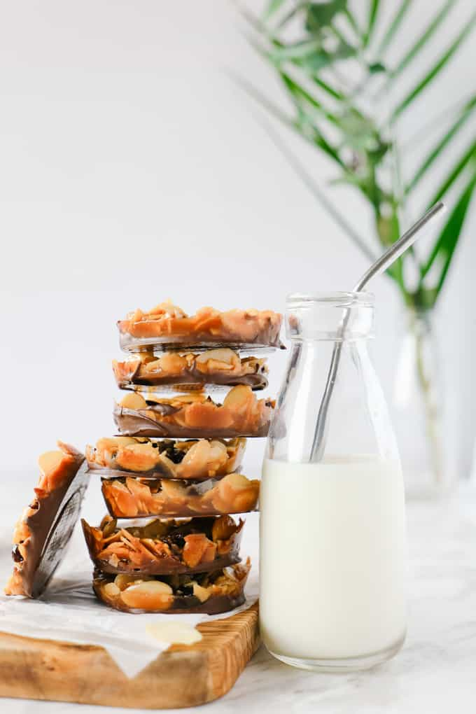 Florentine cookies stacked against a milk bottle.