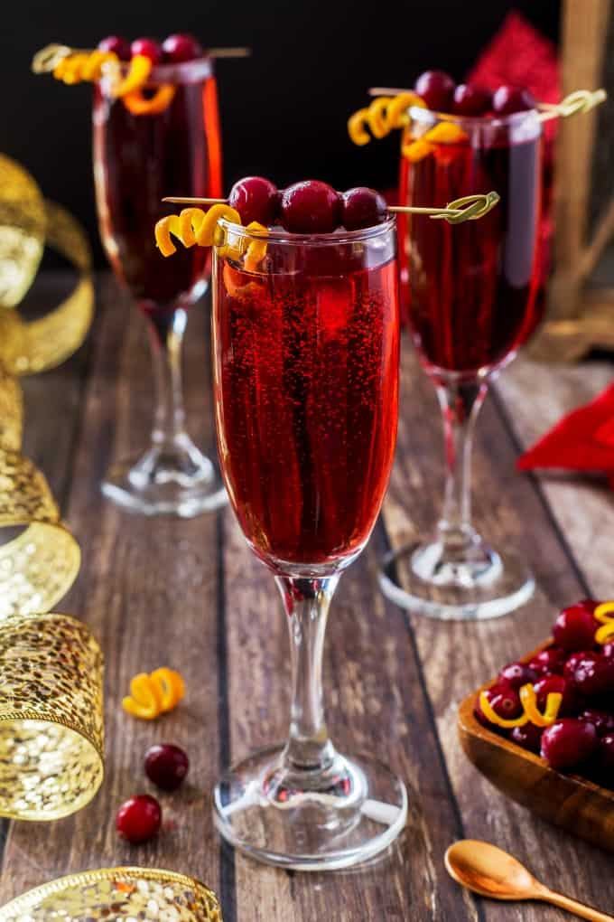 Three Poinsettia Drinks garnished with cranberries and orange twists