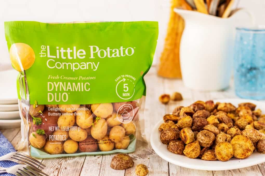 Package of Dynamic Duo potatoes beside a plate of roasted potatoes.