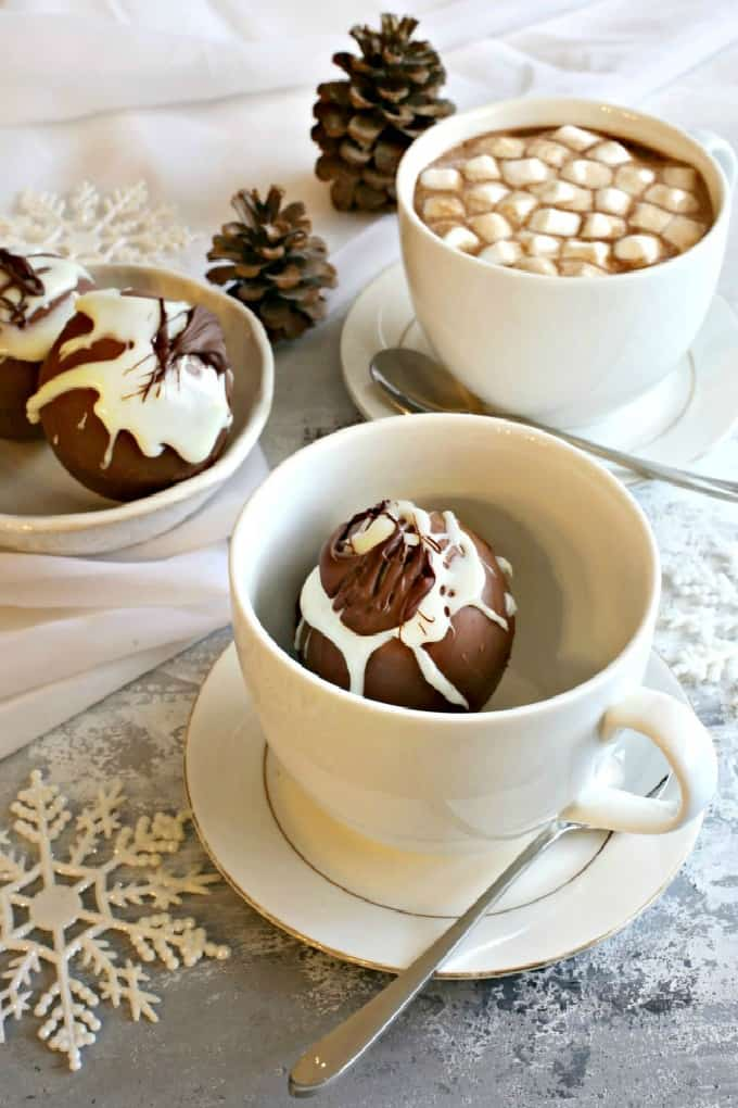 Hot Chocolate Bomb in a cup and saucer with a hot chocolate in another cup.