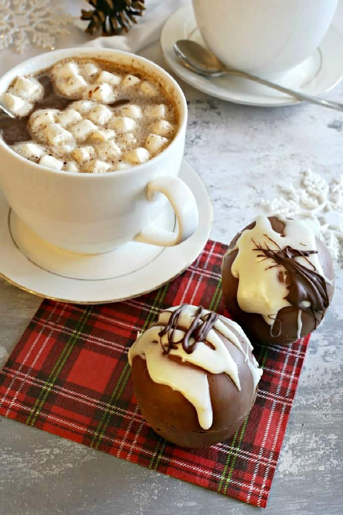 Hot cocoa in a mug with cocoa bombs on plaid