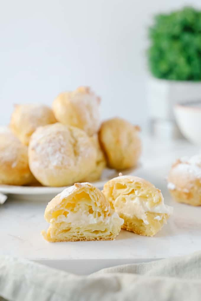Cream puffs with one sliced in half in the front