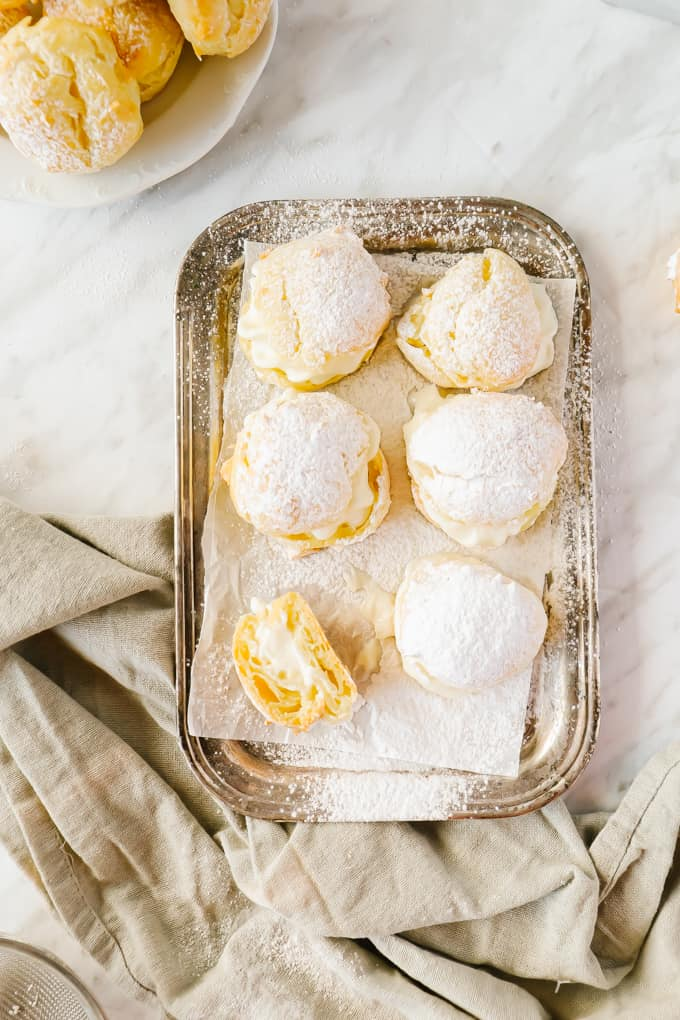 Cream puffs on a silver platter dusted with icing sugar
