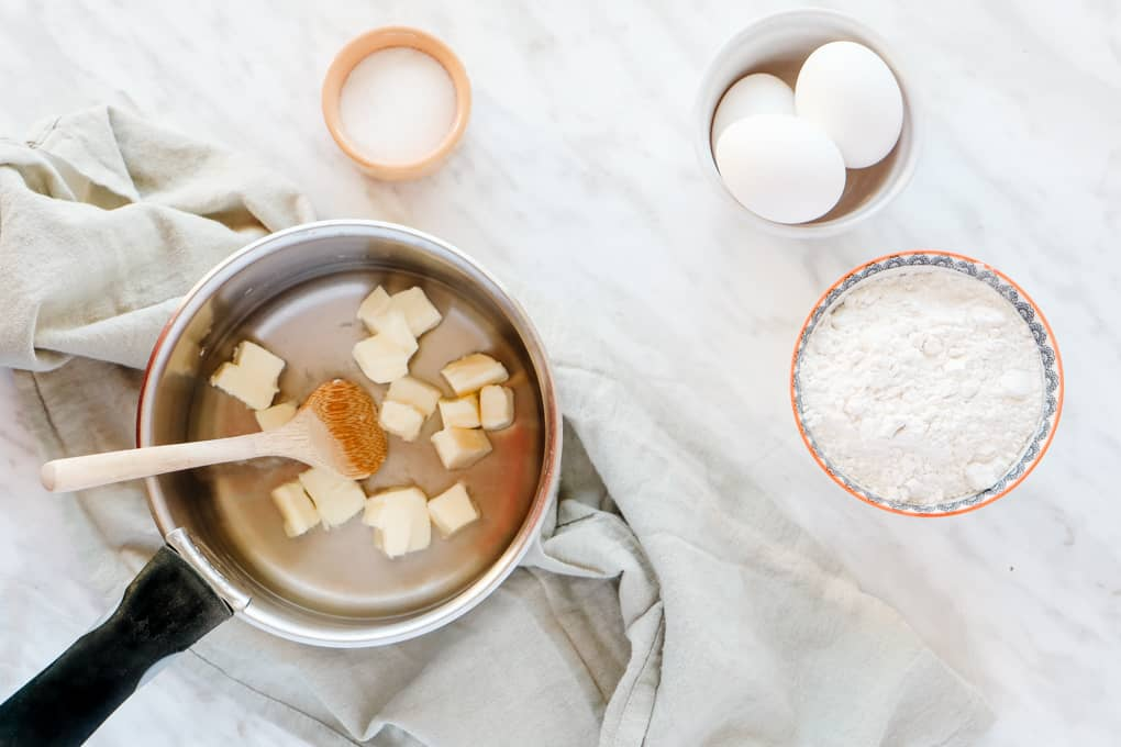 Butter cubed in a saucepan, eggs in a small cup and dry ingredients in bowls.