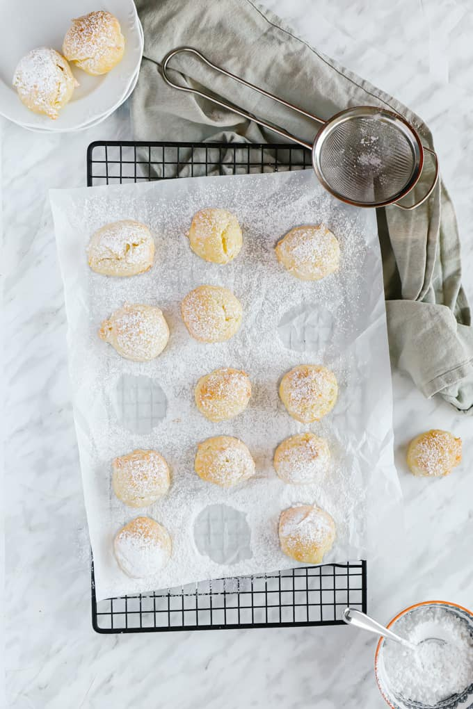 Cream puffs on parchment on a cooling rack