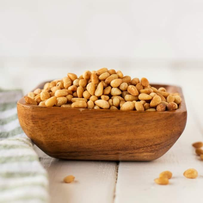 Toasted pine nuts in a wooden bowl.