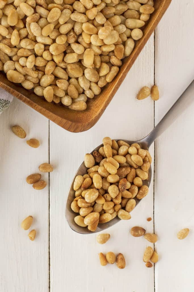 Spoon full of toasted pine nuts and also in a bowl