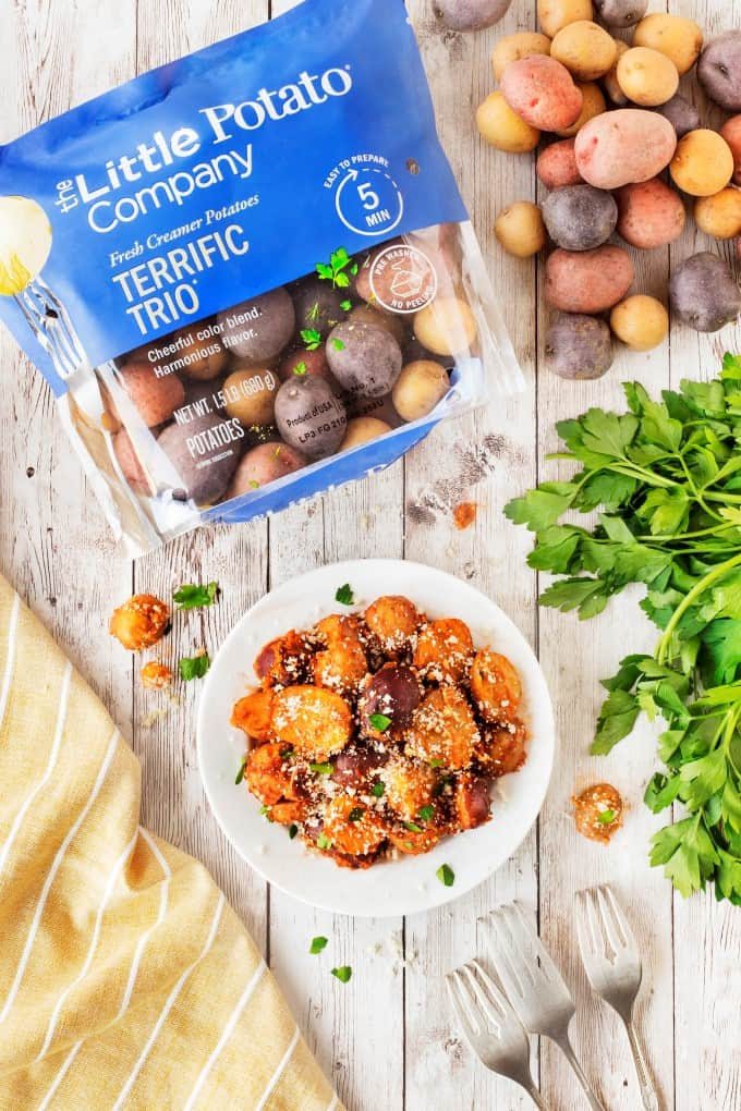 Red Pesto Potatoes on a plate with a bag of Terrific Trio Little potatoes