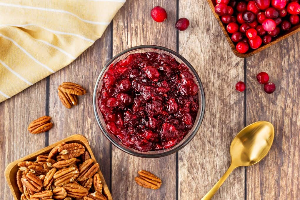 Overhead horizontal shot of cranberry sauce with pecans and cranberries scattered and in dishes.