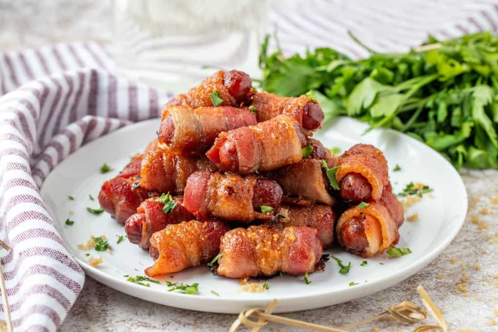 Bacon wrapped smokies on a plate.