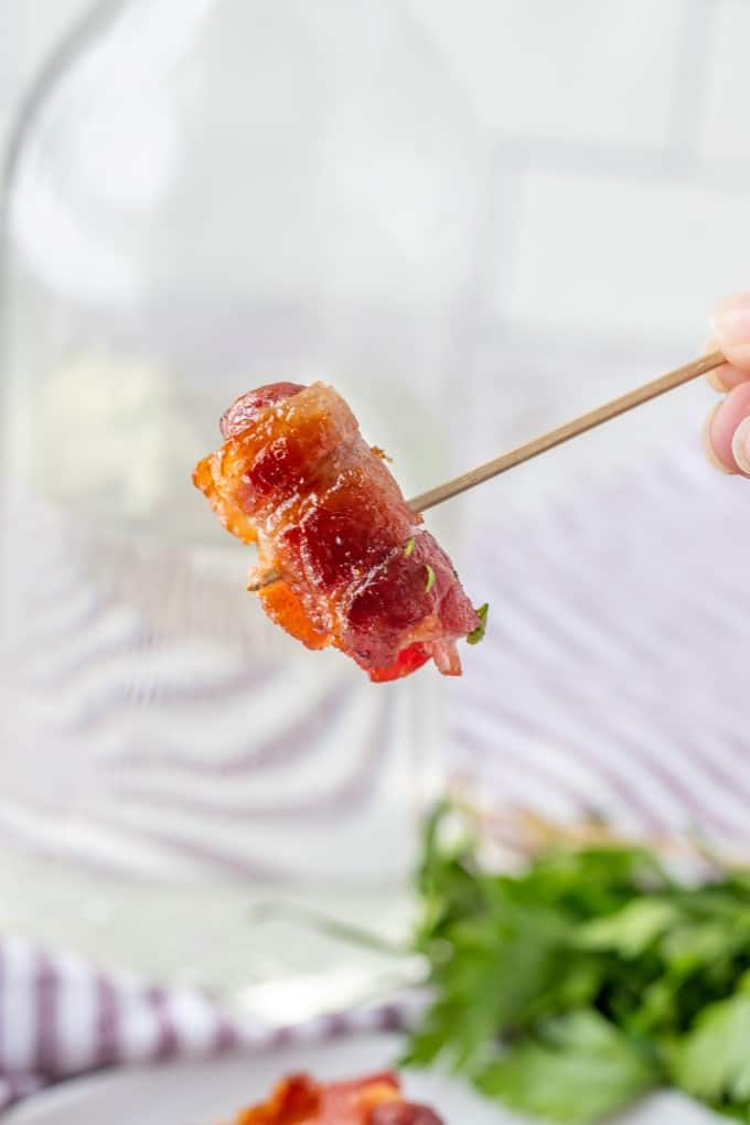 A closeup of a bacon wrapped smokie.