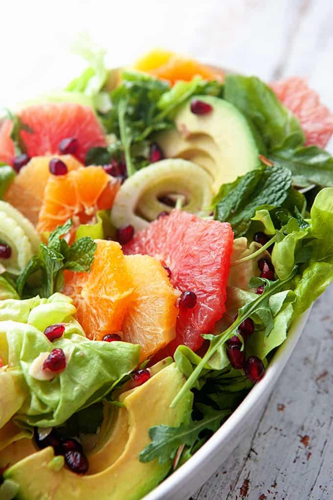 Close up of a greens, oranges, grapefruits, avocado and pomegranate seeds in a bowl.
